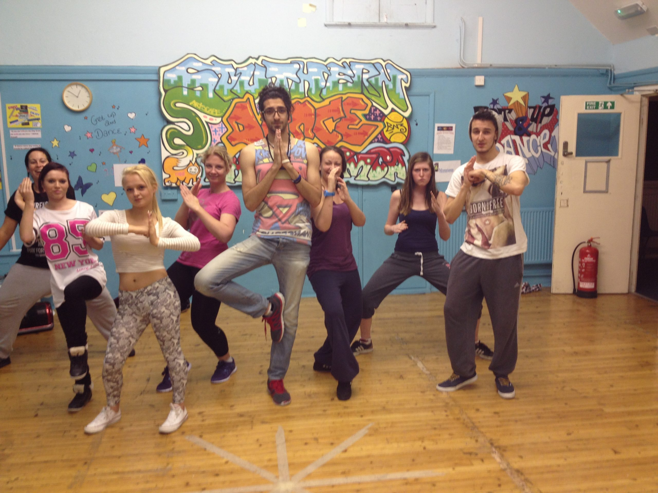 YMCA DLG young people doing martial arts animal poses at a dance workshop